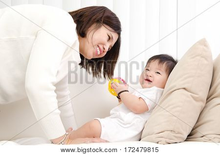 Asian mother playing with her baby on sofa