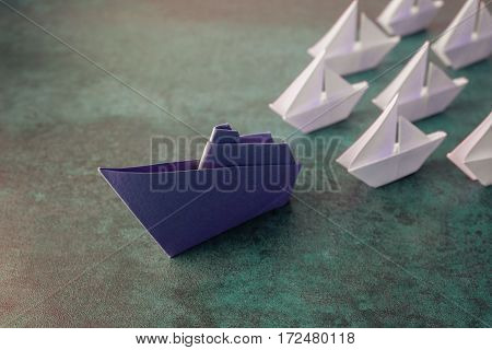 Origami paper ship with small sailboats leadership concept toning