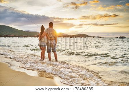romantic couple with feet in water watching sunset over koh samui thailand