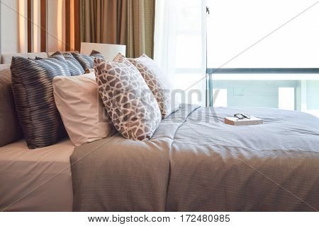 Stylish Bedroom Interior Design With Brown Pillows And Book On Bed