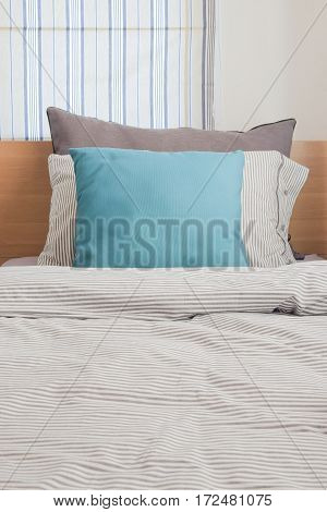 Turquoise And Gray Pillow On Bed With Stripe Pattern Bedding Style