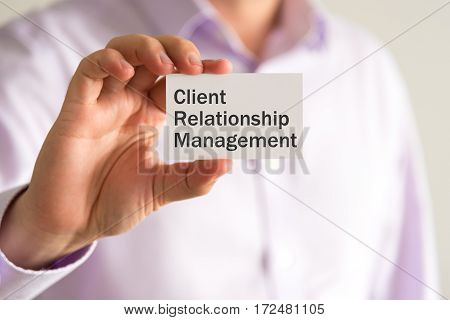 Businessman Holding A Card With Text Crm Client Relationship Management