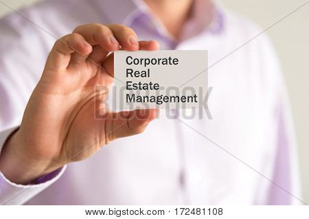 Businessman Holding A Card With Text Corporate Real Estate Management