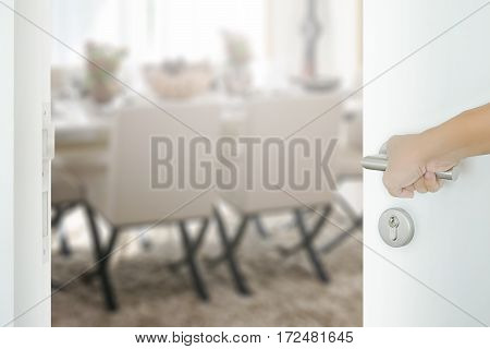 Man Hand Opening White Door To Dining Room With Dining Table And Comfortable Chairs