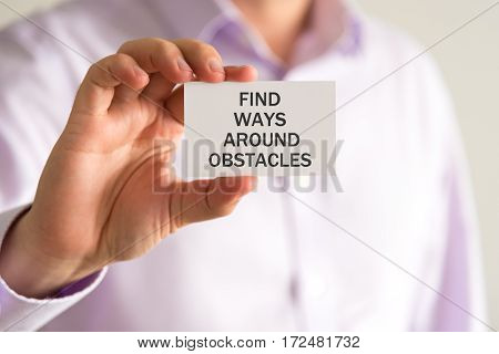 Businessman Holding A Card With Text Find Ways Around Obstacles
