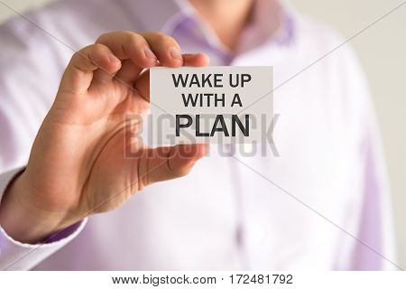 Businessman Holding A Card With Text Wake Up With A Plan
