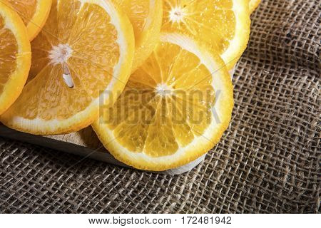 Orange slices on wooden cutting board on jute bag