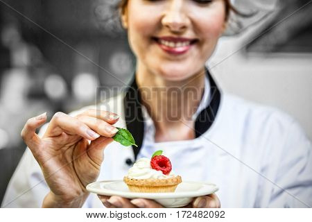 Smiling half head chef putting mint leaf on little cake on plate in professional kitchen