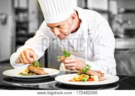 Closeup of a concentrated male chef garnishing food in the kitchen