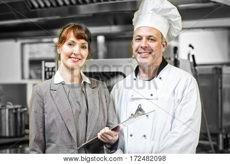 Mature head cook posing with female manager in professional kitchen