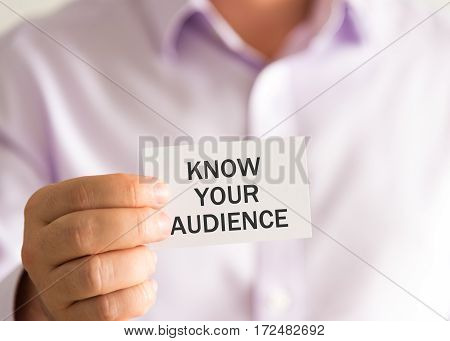 Businessman Holding A Card With Text Know Your Audience
