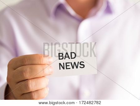 Businessman Holding A Card With Text Bad News