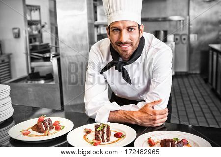 Happy chef looking at camera behind counter of desserts in a professional kitchen