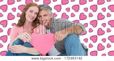 Casual couple holding pink heart against background with hearts