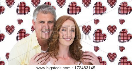 Casual couple hugging and smiling against background with hearts