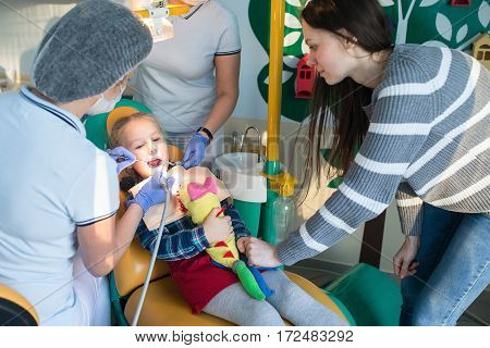 child with his mother in the dentist office treated teeth