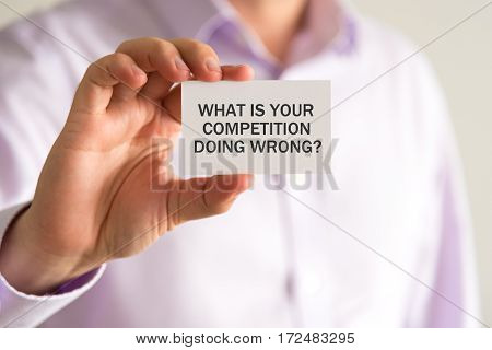 Businessman Holding A Card With Text What Is Your Competition Doing Wrong ?