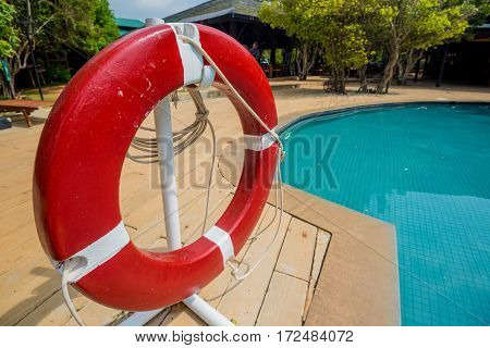 Red lifebuoy near swimming pool at tropical hotel