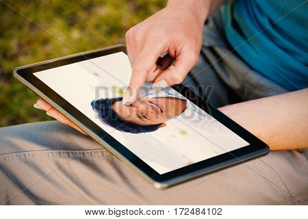 Smiling man looking at camera against midsection of woman using digital tablet