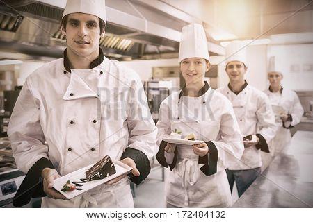 Chefs presenting deserts in the kitchen