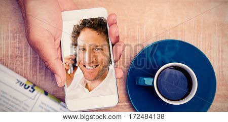 Person using smart phone by coffee and document on table against closeup portrait of smiling man using mobile phone