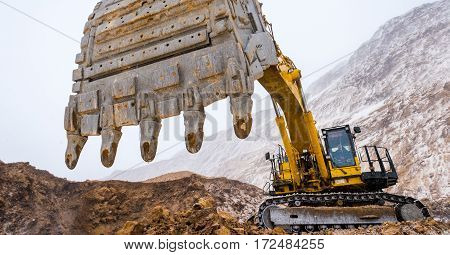 Big yellow excavator at an open pit mining