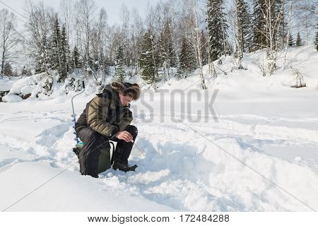 the fisherman catches fish on the river in the winter
