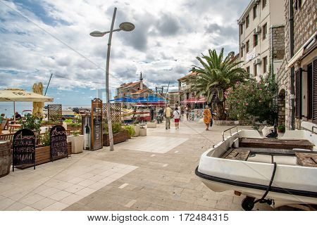 PETROVAC, MONTENEGRO - SEPTEMBER 20, 2016:Tourists walk along the promenade in Petrovac, Montenegro.