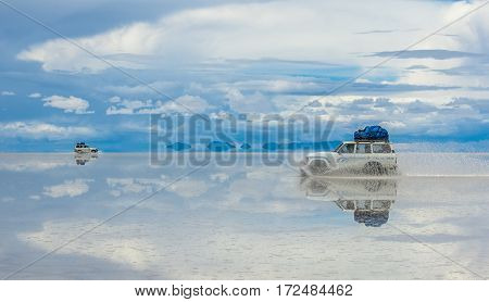 Off-road vehicles driving in Salar de Uyuni Bolivia the world's largest salt flat