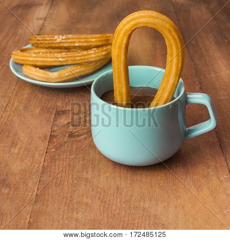 Square photo of churros, traditional Spanish, especially Madrid, dessert, in the form of horseshoe, with a cup of chocolate on a wooden board texture, retro style, with copyspace