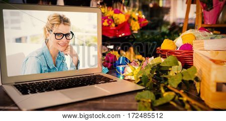 Laptop on table with leaves and ribbons against designer wearing glasses