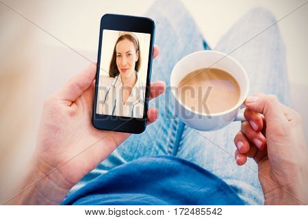 Woman using her mobile phone and holding cup of coffee against close-up portrait of smiling woman
