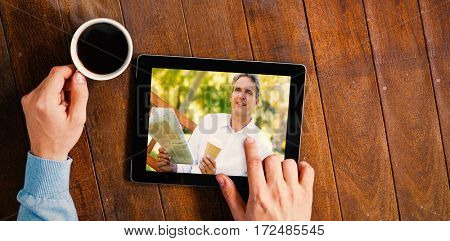 Businessman holding newspaper and coffee cup in park against man using digital tablet while having cup of coffee