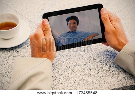 Businessman holding small tablet at table against happy man relaxing on couch