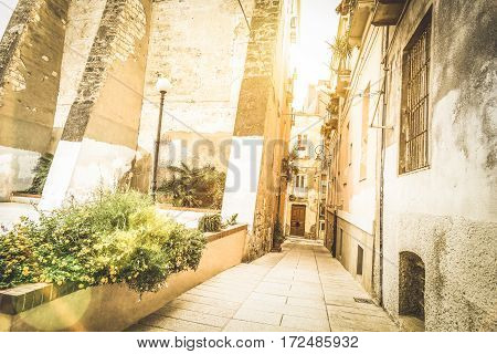 Medieval narrow street in the old city of Cagliari at sunset - World famous european city in the italian region of Sardinia - Wanderlust and travel concept on Italy destinations - Warm sunshine filter