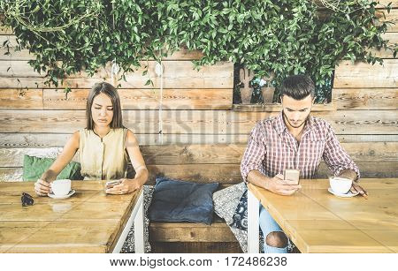 Fashion couple in disinterest moment ignoring each other using mobile cell phone - Concept of apathy sadness addicted to new technologies - Boyfriend and girlfriend break up with smartphones addiction