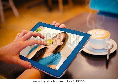 Smiling young woman eating apple against close-up of digital tablet and coffee on table