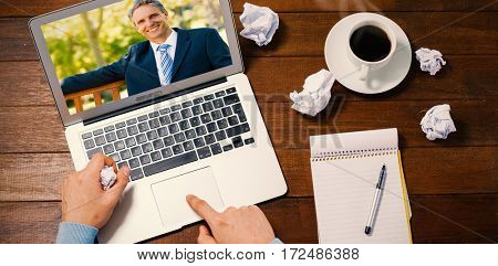 Confident businessman sitting on park bench against man using laptop while writing on notepad