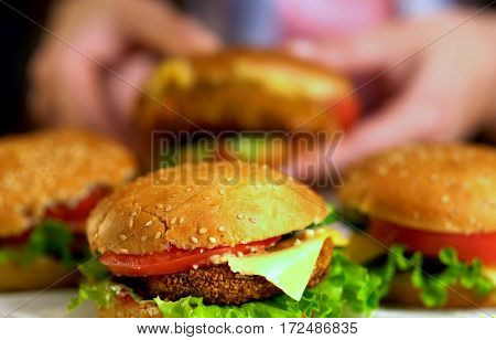 Hamburger fast food with ham on wooden board . Group of hamburger. Human hand holding cheeseburger is not in field. Snack for friends.