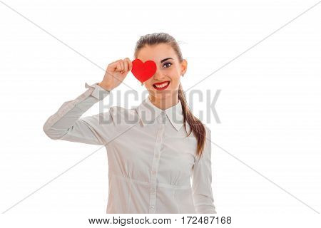 smiling young girl in shirt keeps Valentine near eyes isolated on white background