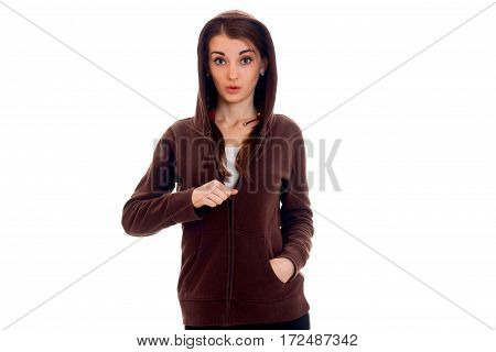 a young girl stands in jacket with a hood with a surprised face isolated on white background