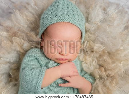 lovely newborn baby in hat and overalls sleeping with hands on chest, top view