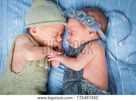 newborn twins - a boy and a girl sleeping on a blue blanket closeup