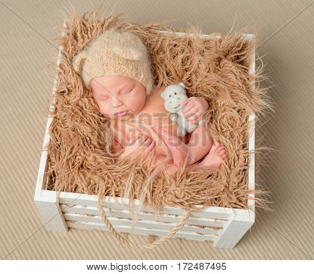 sweet sleeping newborn baby with little toy in wooden box with fluffy blaket