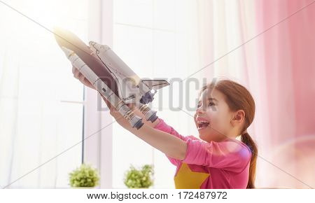 Child girl playing with toy rocket and dreaming of becoming a spacemen. Portrait of funny kid near windows.
