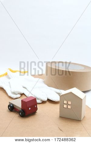 Toy mini car truck, packing tape, card boards, cotton work gloves and house on white background. Distribution concept.