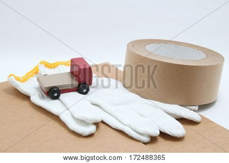 Toy mini car truck, packing tape, card boards, and cotton work gloves on white background. Distribution concept.