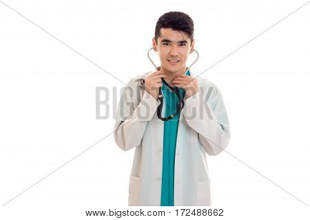 a young doctor in a white lab coat stethoscope into his ears and smiling isolated on white