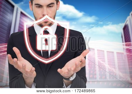 Cheerful businessman presenting with his hands against composite image of server towers