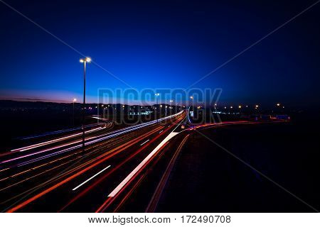 Traffic at night on the highway with headlights trails